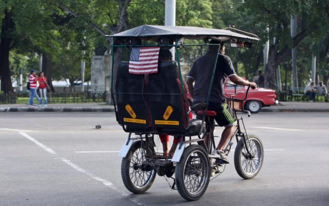 Un bicitaxicon la bandera de EEUU cruza por una calle de La Habana.