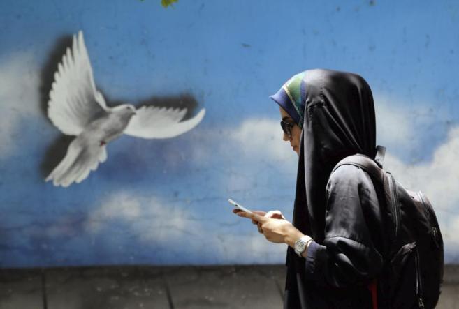 Una mujer iraní revisa su móvil en una calle de Teherán