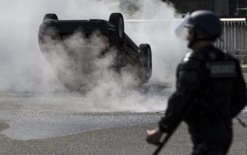 Taxistas franceses contemplan un vehículo ardiendo de Uber en París.