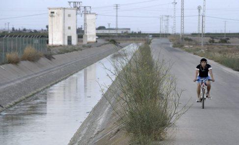 Un joven pasea en bicicleta junto a uno de los canales por los que se...