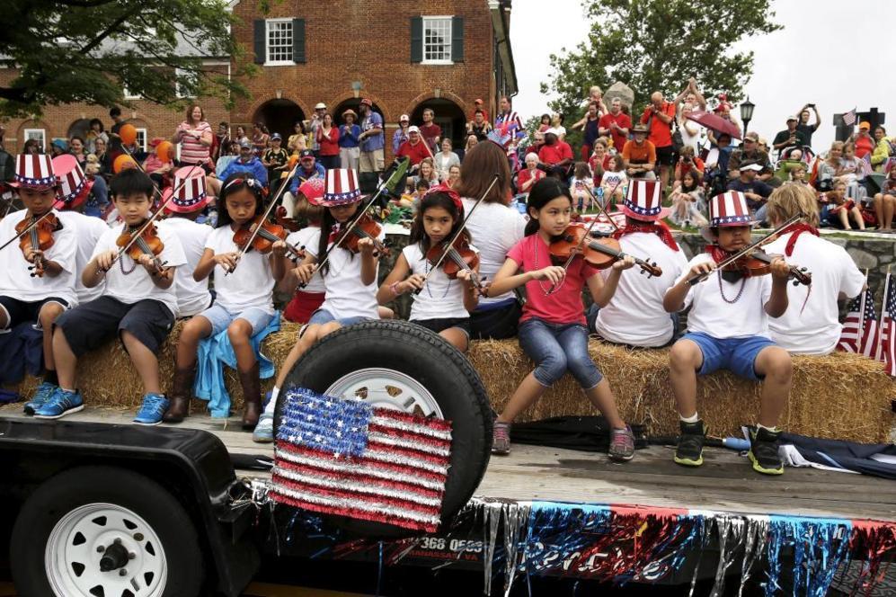 Varios niños tocan el violín en una de las carrozas del desfile del...