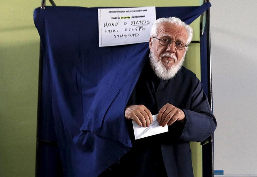 Un sacerdote ortodoxo griego asiste al centro de votación a primera...