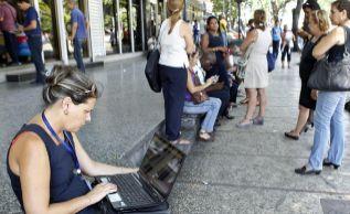 Una mujer con su portátil en una zona con wifi.