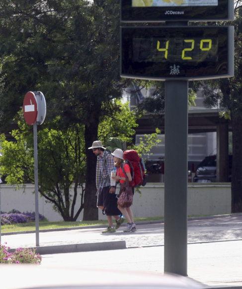 Unos turistas pasan junto a un termómetro por el centro de Córdoba...