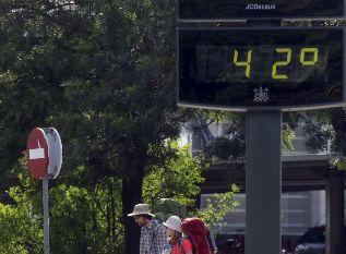 Unos turistas pasan junto a un termómetro en Córdoba.