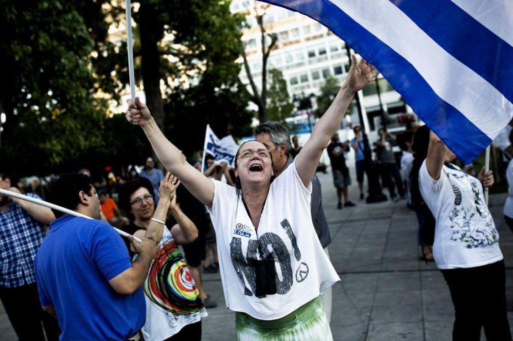 Una mujer celebra en la plaza Sintagma de Atenas los primeros datos...