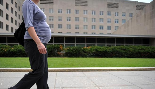 Una mujer embarazada pasa por delante del edificio del Departamento de...