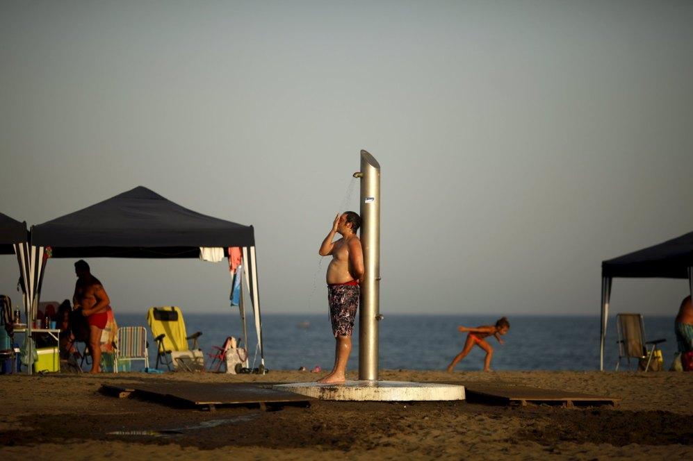 Un hombre se refresca en la ducha en la playa de Sacaba en Málaga...
