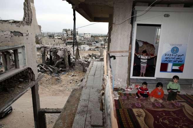 Niños palestinos juegan en su derruida casa en el barrio de Shejaiya,...