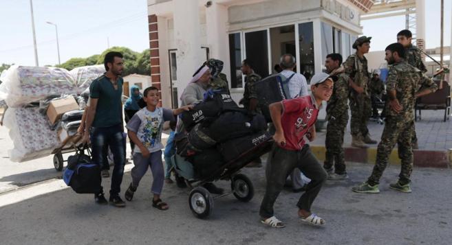 Soldados kurdos vigilan el paso de refugiados sirios desde Turquía a...