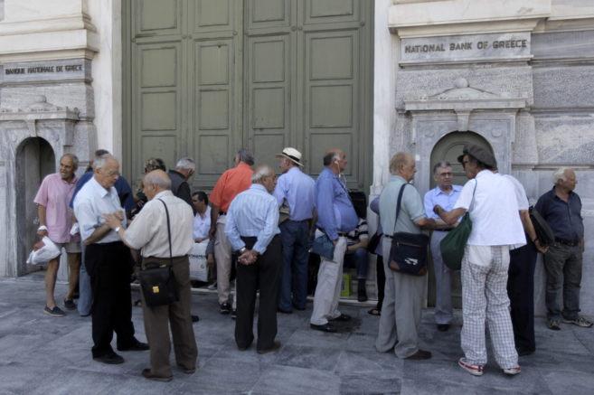 Pensionistas hacen cola en una sucursal del Banco Nacional de Grecia...