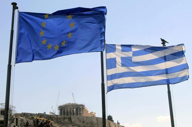 Una bandera griega y una de la Unión Europea ondean hoy junto al...