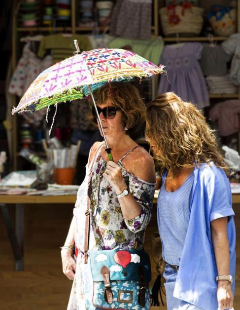 Dos mujeres intentan protegerse del sol, en Valencia.