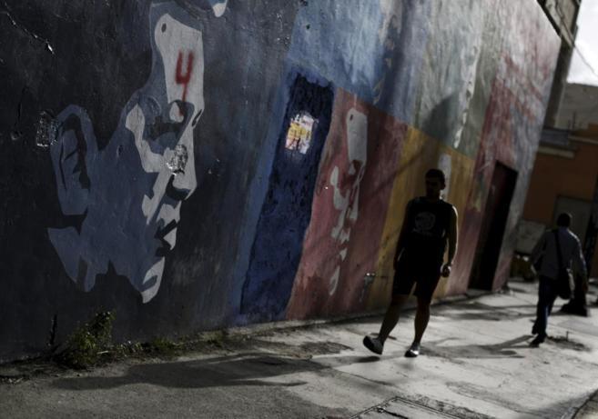 Un hombre pasa por delante de un mural con la cara el ex presidente...