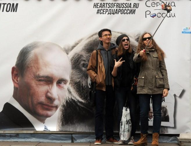 Tres jóvenes se hacen un 'selfie' frente a un mural en San...