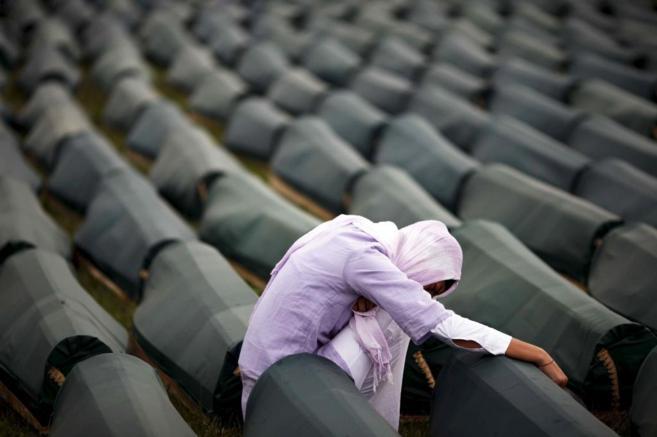 Una mujer reza ante los ataúdes de algunas víctimas de Srebrenica,...