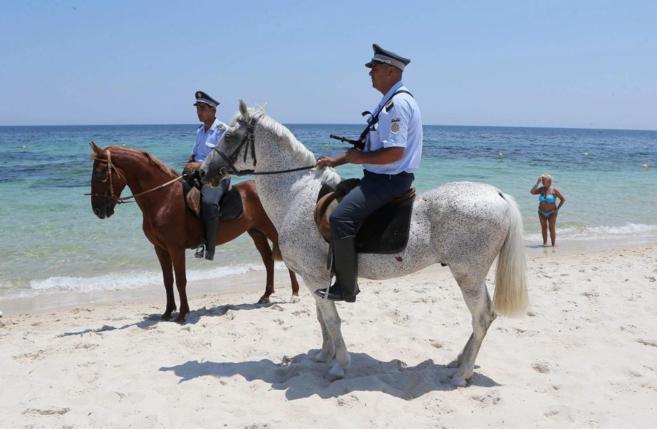 Miembros de las fuerzas de seguridad vigilan la playa de Susa en la...