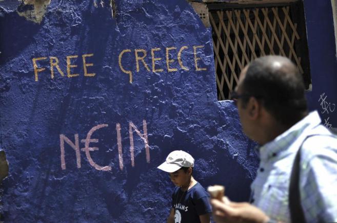 Un hombre lee el grafiti 'Grecia libre'