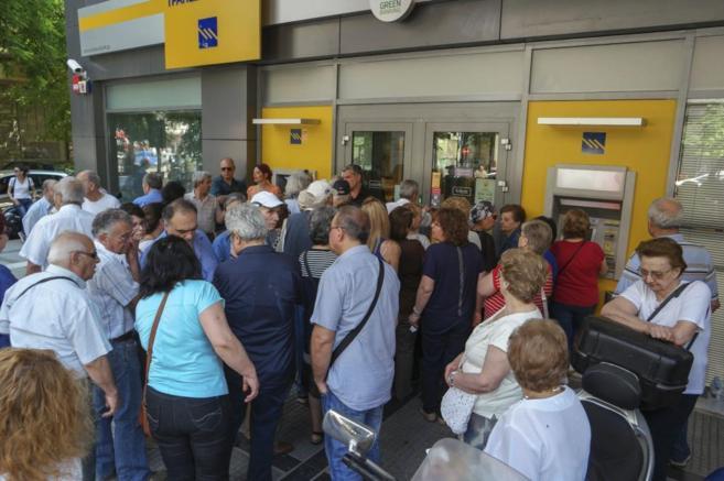 Ciudadanos griegos hacen cola ante una sucursal bancaria griega.