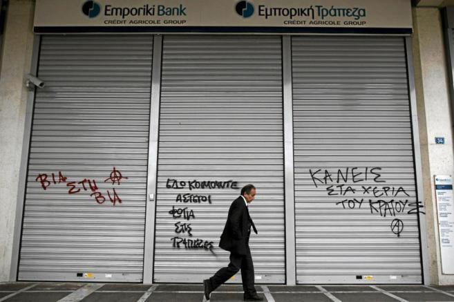 Un hombre pasa frente a una sucursal bancaria cerrada en Atenas.