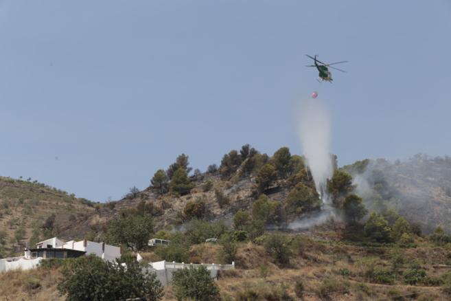 Un helicóptero descarga agua sobre las llamas en la Alpujarra baja de...