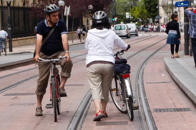 Dos personas en bicicleta sobre las vías del tranvía de Vitoria.