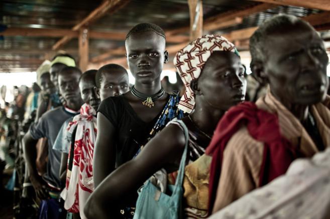 Un grupo de personas aguarda la distribución de comida en un campo de...