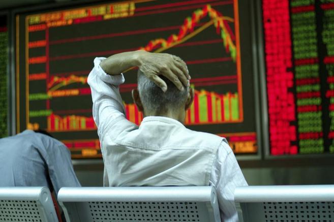 Un inversor en Pekín observa la fuerte caída de la Bolsa, el pasado...
