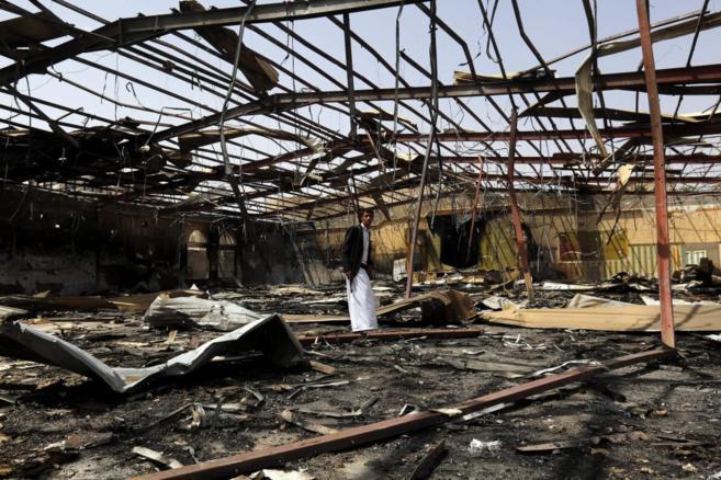 Un miliciano hutí inspecciona los restos de un edificio destrozado...