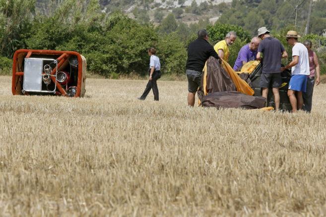Varias personas inspeccionan el globo aeroestático siniestrado.