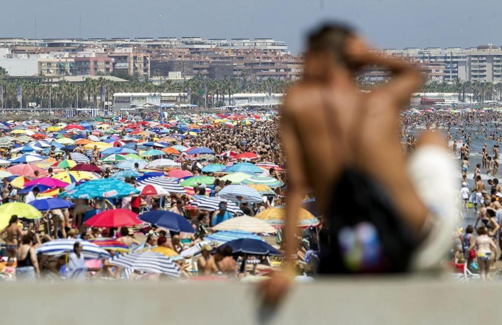 Un joven, sentado en el espigón del puerto de Valencia, observa a los...