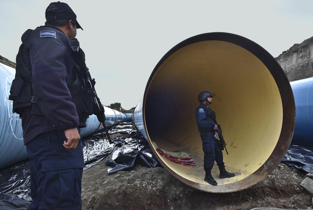 Policías mexicanos inspeccionan una de las tuberías en construcción...