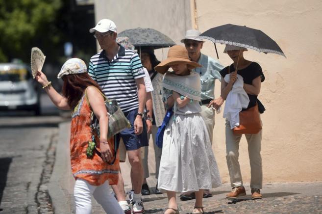 Turistas refugiándose bajo el parasol tras superar de nuevo los 40...
