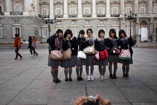 Un grupo de turistas japonesas posa frente al Palacio Real de Madrid.
