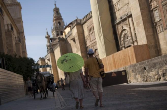 Unos turistas protegida con una sombrilla pasea junto a la Mezquita de...