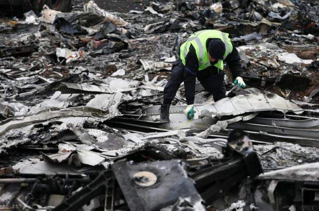 Un investigador holandés recoge restos del avión siniestrado MH17 de...