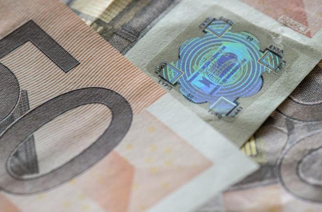Un billete falso de 50 euros que cuenta con un holograma pegado,...