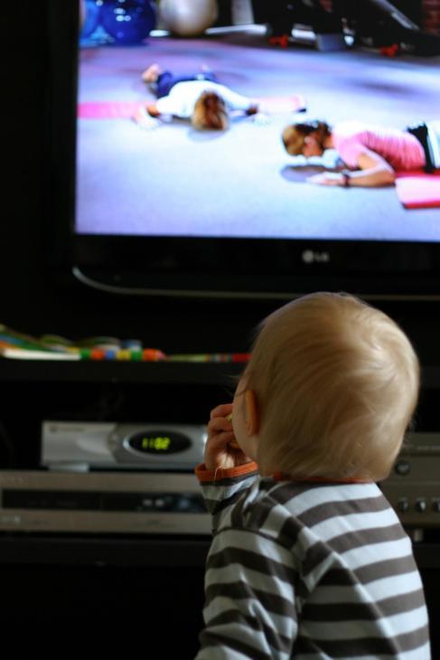 Un niño pequeño viendo la televisión.