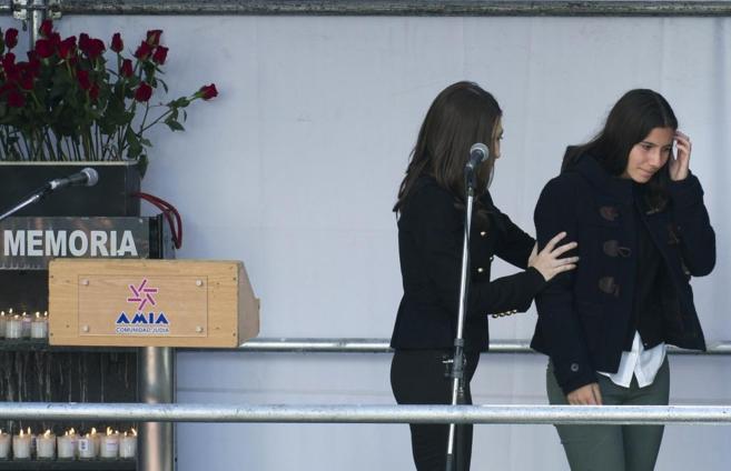 Iara Nisman consolada por una mujer que enciende una vela.