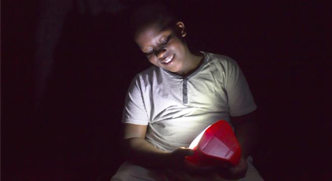 Un niño utiliza una de las lámpara solares de d.light.