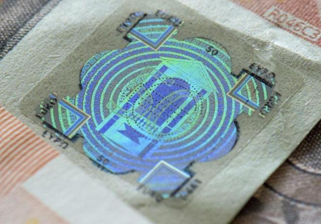 Imagen que muestra un falso holograma pegado a un falso billete de 50...