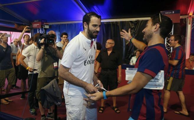 Un simpatizante del Real Madrid saluda a un amigo, socio del FC...