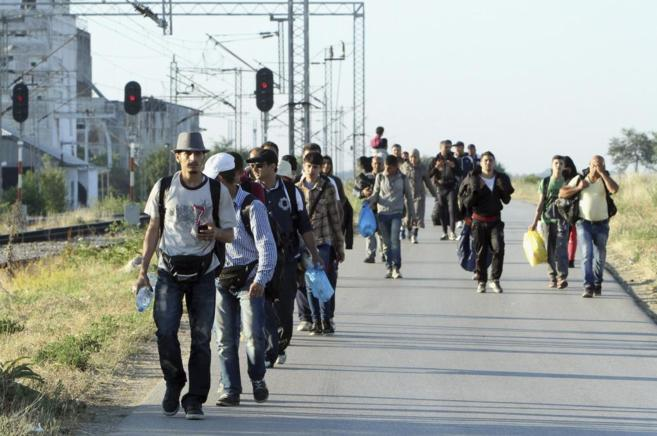 Un grupo de inmigrantes sirios camina por la frontera que separa...