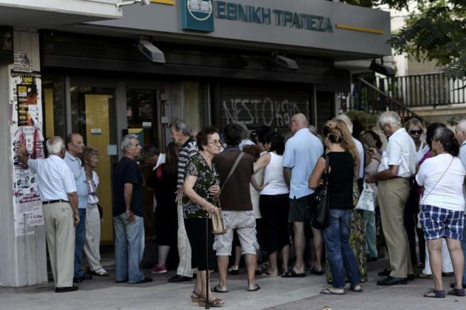 Personas esperando en la sucursal de un banco antes de su apertura.
