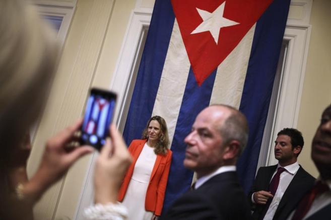 Invitados se fotografían con la bandera cubana, en la apertura de la...