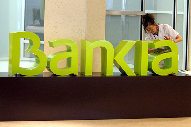 Una operaria limpia el logo de Bankia en una de las sucursales