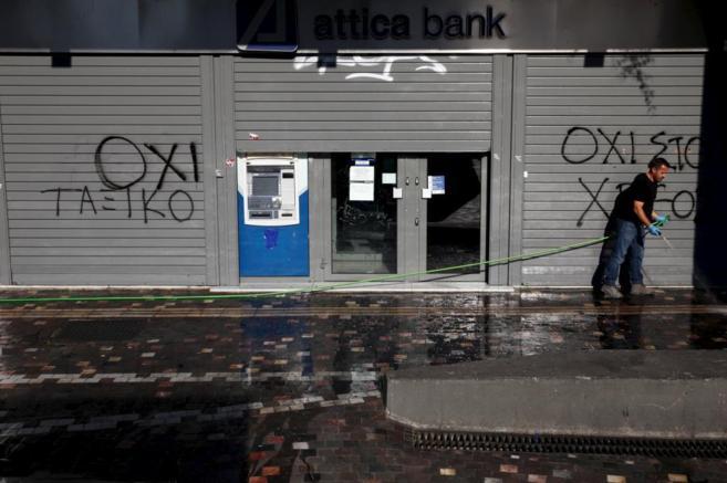 Un hombre limpia la acera en la sucursal del Banco Attica, en Atenas