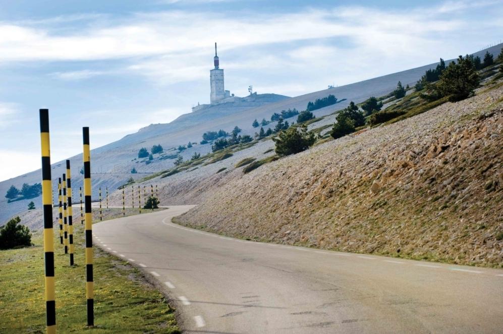 """<b>MONT VENTOUX*</b>  (Vaucluse/ Provenza-Alpes-Costa Azul, Francia). Altitud: 1.912 metros / Longitud 21.2 km / Pendiente media: 7.15% / Pendiente máxima: 12% (rampas en km 7 y 21). La montaña de los vientos infernales, la montaña asesina, un paisaje lunar coronado por una torre de telecomunicaciones de 50 metros de altura, que impone. """"Su clima (más que una ubicación geográfica) lo convierte en un terreno maldito, en una prueba para héroes, una especie de infierno en las alturas"""" (<b>Roland Barthes</b>). Allí se volvió loco el suizo <b>Ferdi Kubler</b> en su escalada de 1955 y Tom Simpson, campeón del mundo en 1966, reventó fulminado un trágico 13 de julio de 1967 a dos km de la cima, víctima del esfuerzo y de su cóctel mortal de anfetaminas. La falta de oxígeno y de vegetación por sus laderas 'lunares', sus rampas imponentes, la hacen de las más temibles para el pelotón, donde se acumulan algunas de las más sonoras pájaras del ciclismo."""