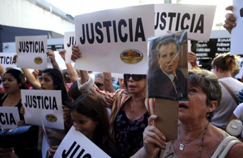 Una mujer sostiene una foto del fiscal argentino Alberto Nisman en una...