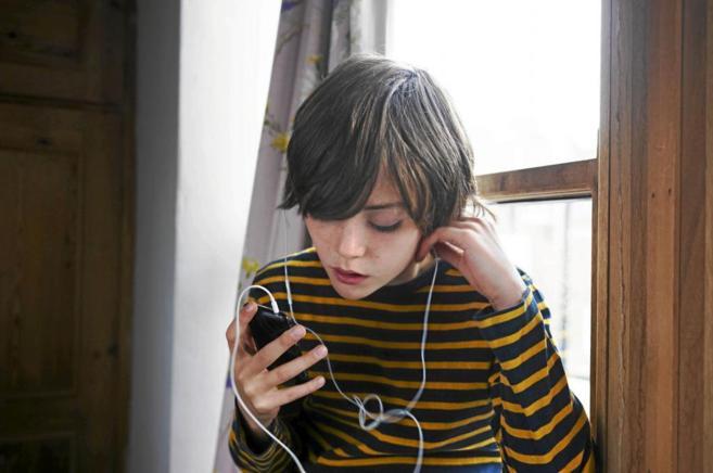 Un chico escuchando música en el móvil.